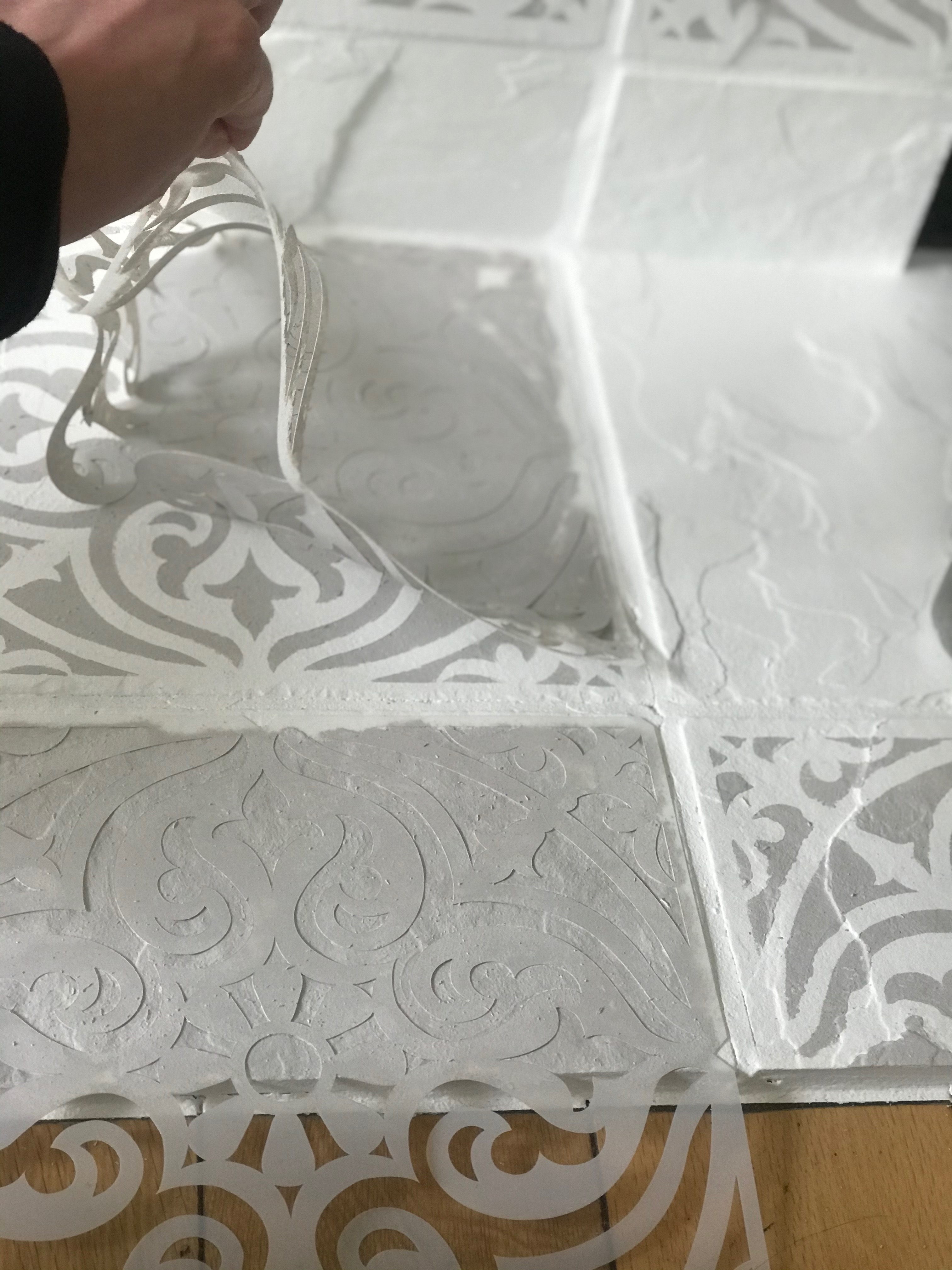 Removing a DIY stencil from a fireplace mantel makeover