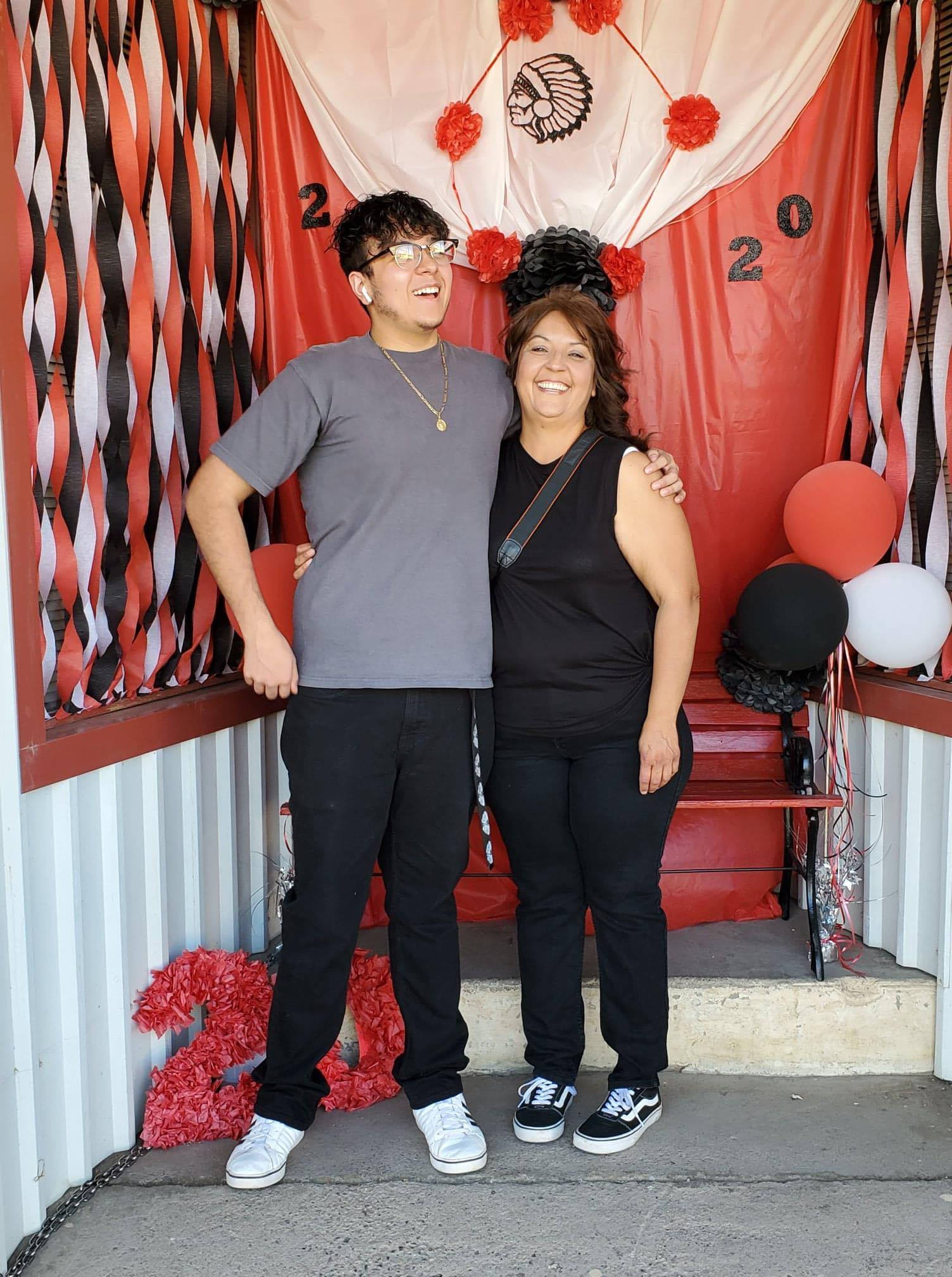 Anna and son Angel Villalobos in front of outdoor Cricut graduation photo booth for Cobre High School