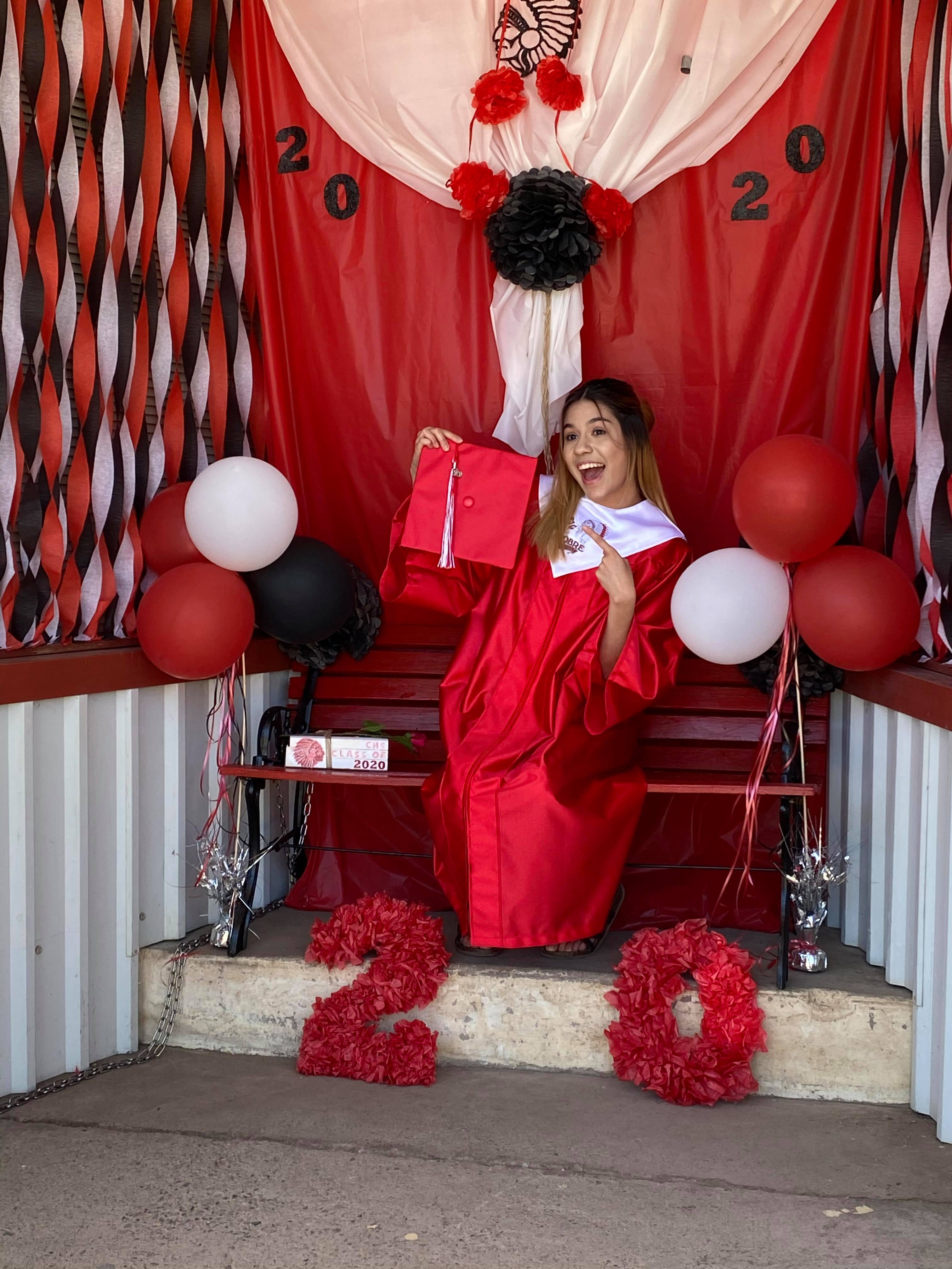 Excited graduate in front of outdoor Cricut graduation photo booth for Cobre High School