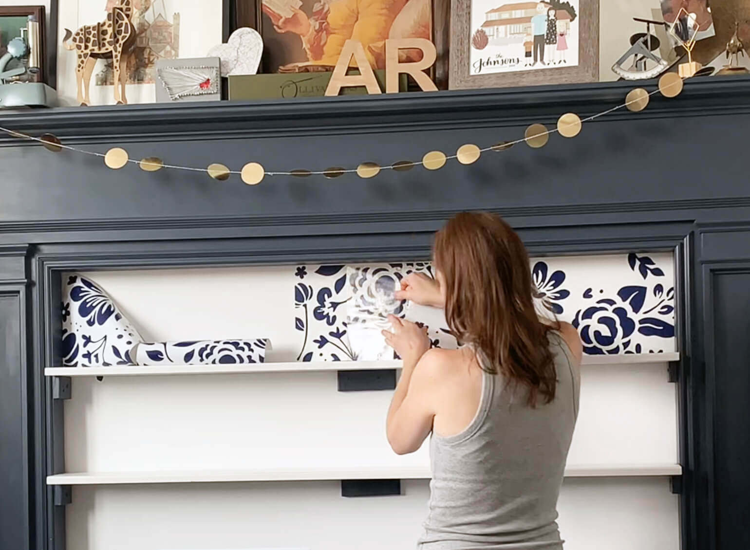 Anna Rose applying the vinyl design to her wall with Cricut transfer tape.