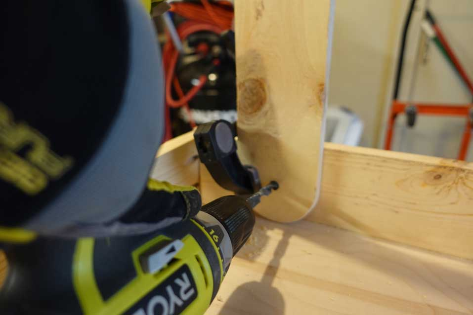 screwing in cornhole board legs with a clamp and drill