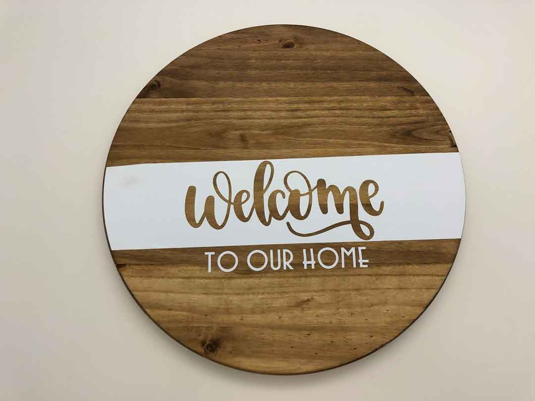 Wood round welcome sign decorated with Cricut iron-on