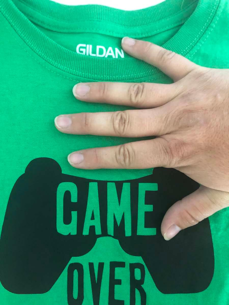 Measuring from the collar to place my Game Over Back-to-School T-shirt made with a Cricut machine and Everyday Iron-On