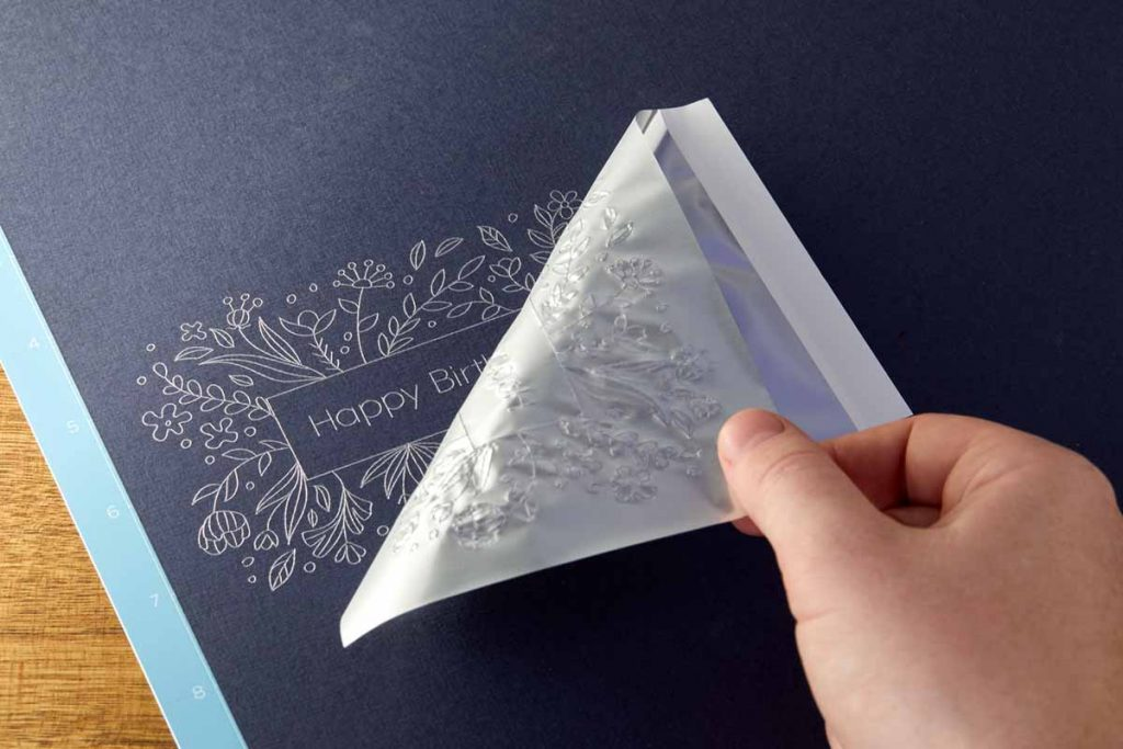 Hand removing transfer foil sheet from completed card