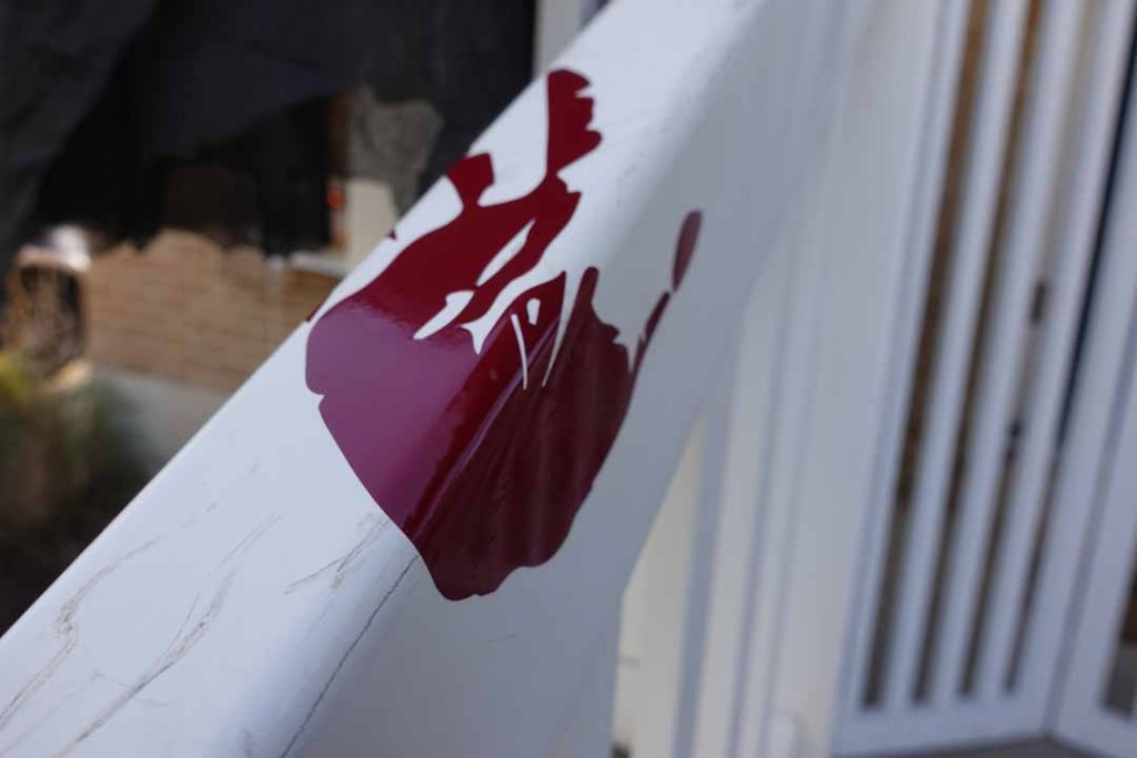 Bloody handprint on front porch banister