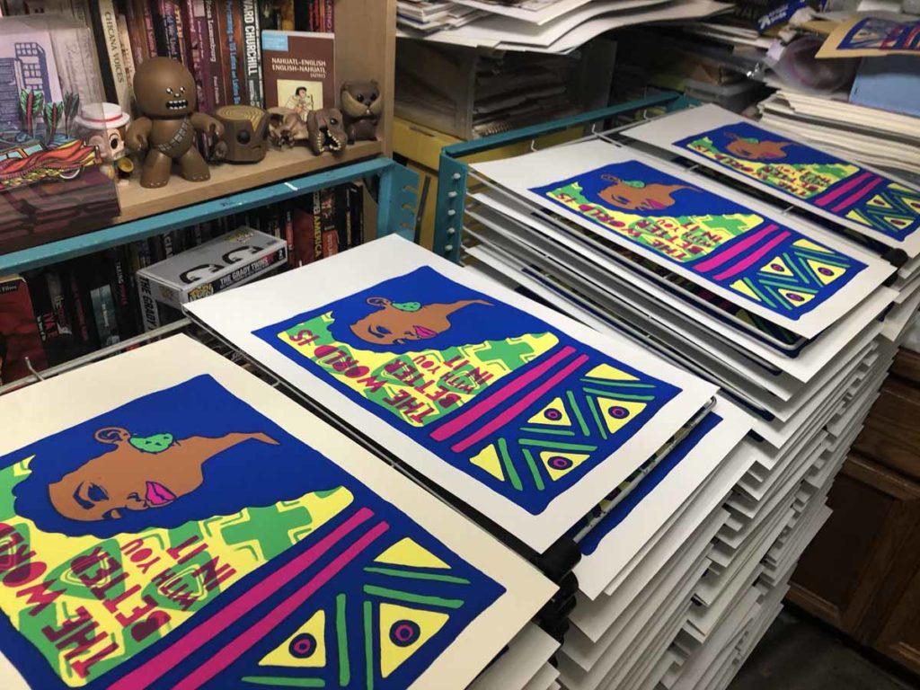 """Multiple prints of """"Esperanza"""" from artist Melanie Cervantes drying on racks"""