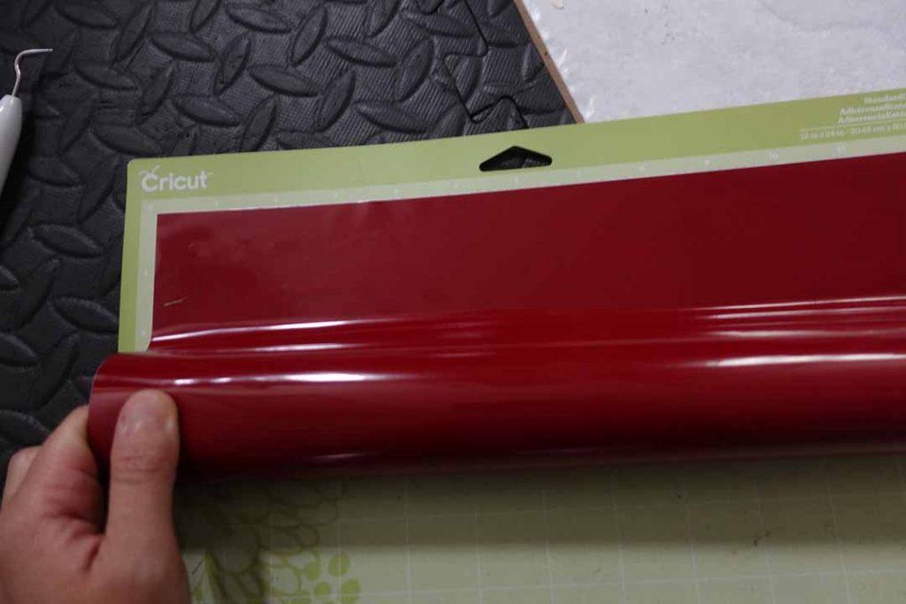 Rolling Cricut vinyl onto its machine mat