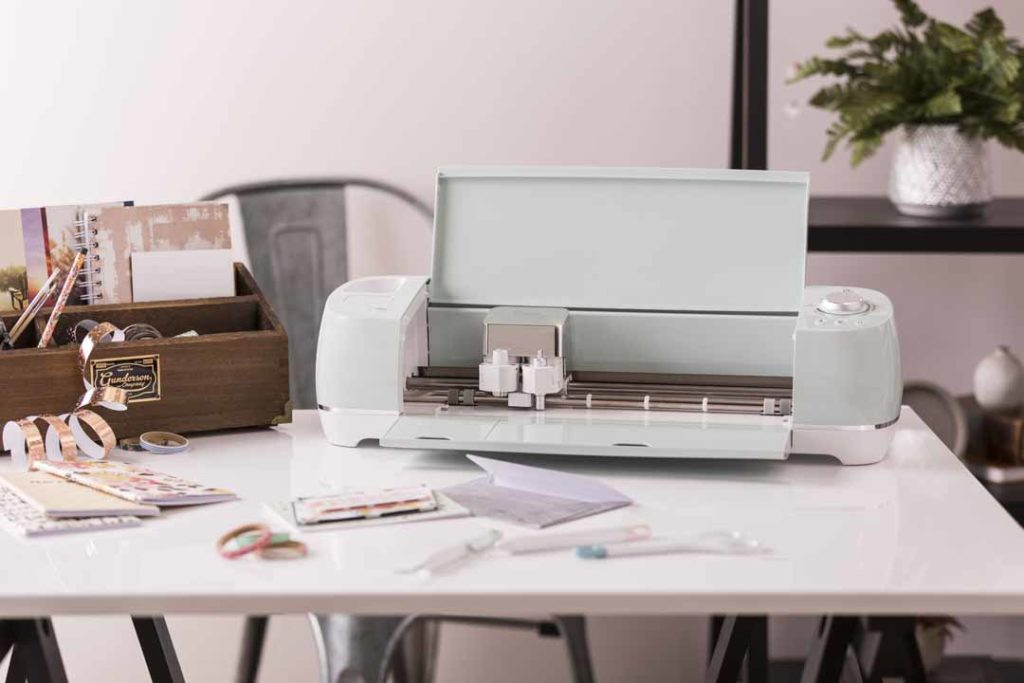 Cricut Explore Air 2 machine on desk with projects