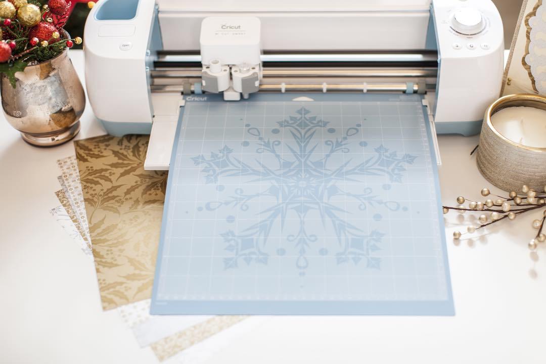 Cricut Maker machine cutting a snowflake with washi paper