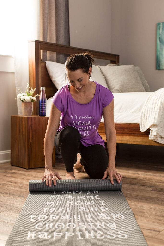 Woman smiling rolling up yoga mat