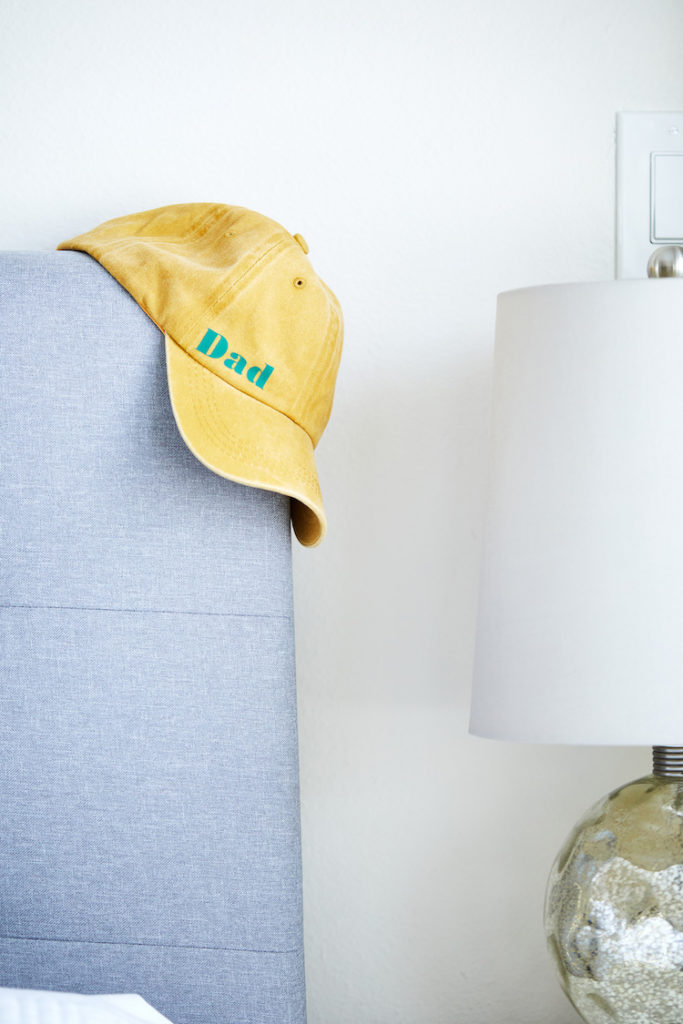 """Dad"" hat hanging on side of bed"