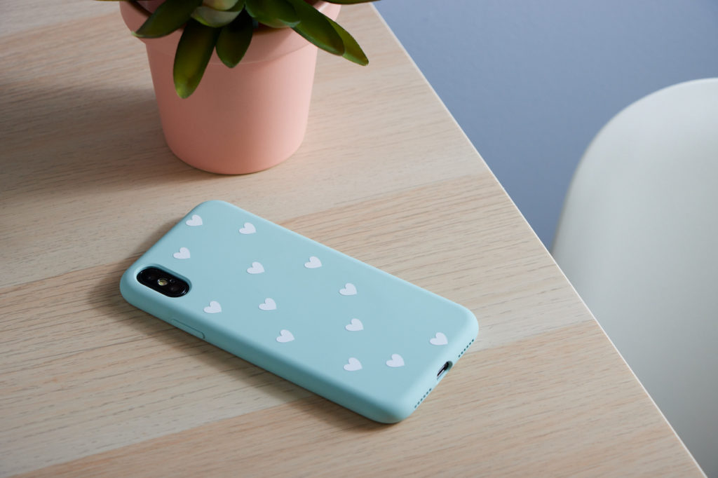 Blue phone case with white vinyl hearts on desk