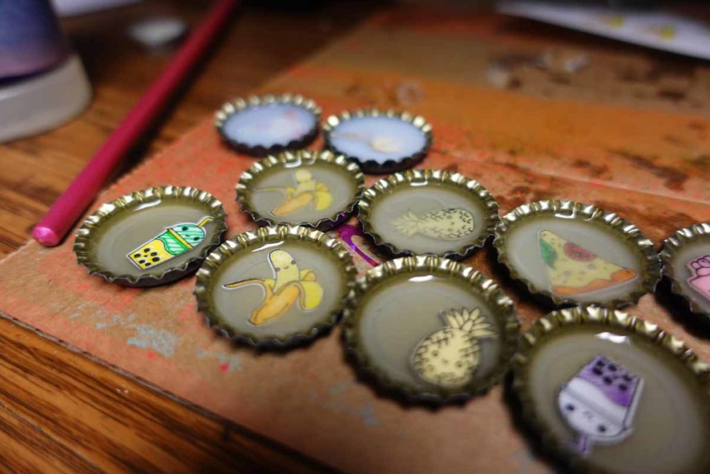 Bottle cap pins made with Cricut Smart Labels and resin or polymer compoound