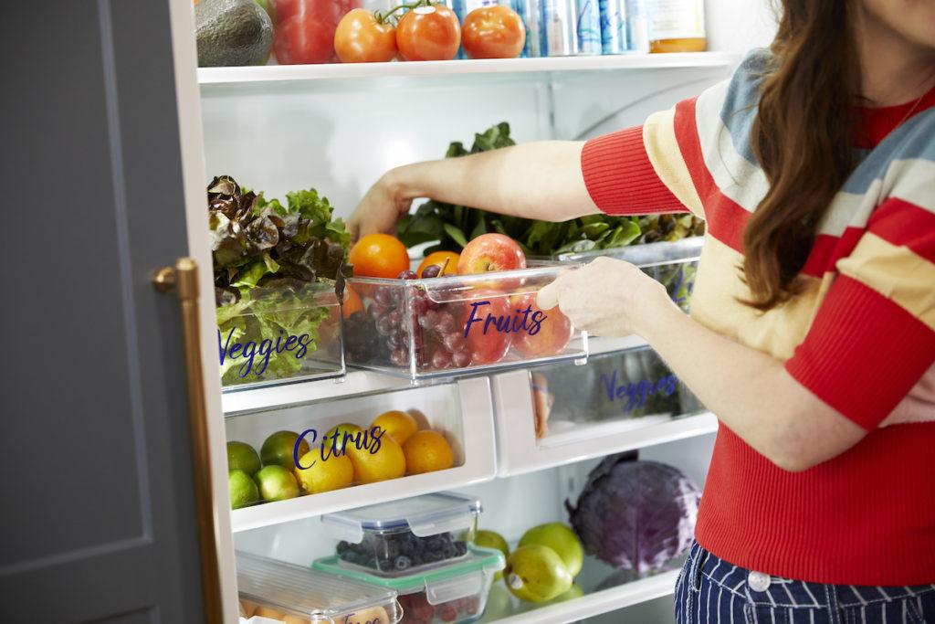 Woman reaching for fruits in fridge