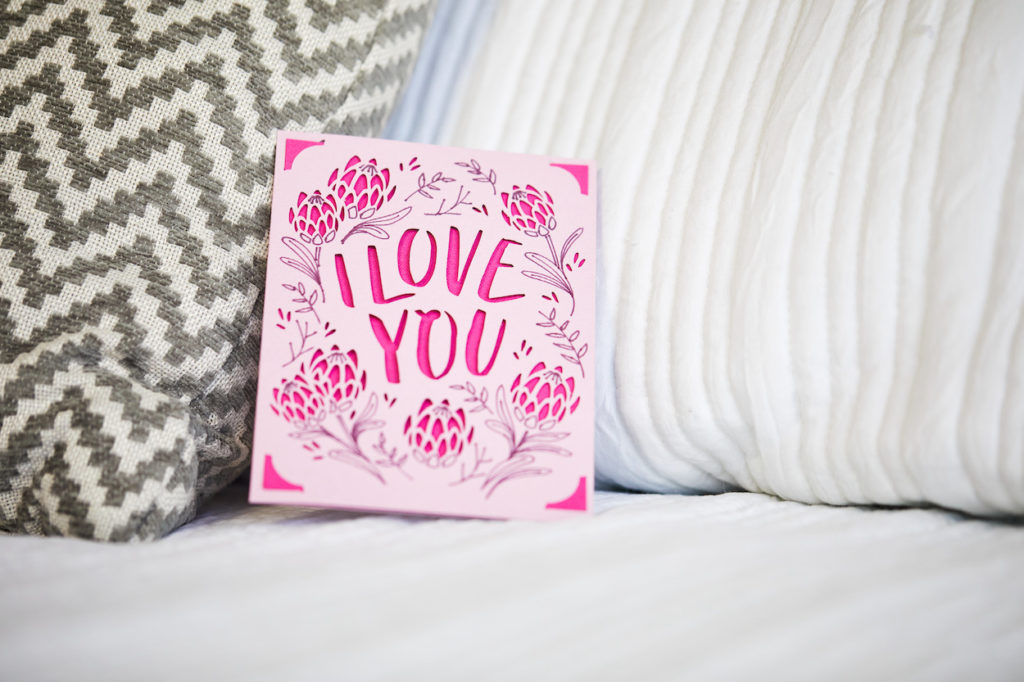 """""""I love you"""" pink greeting card on bed"""