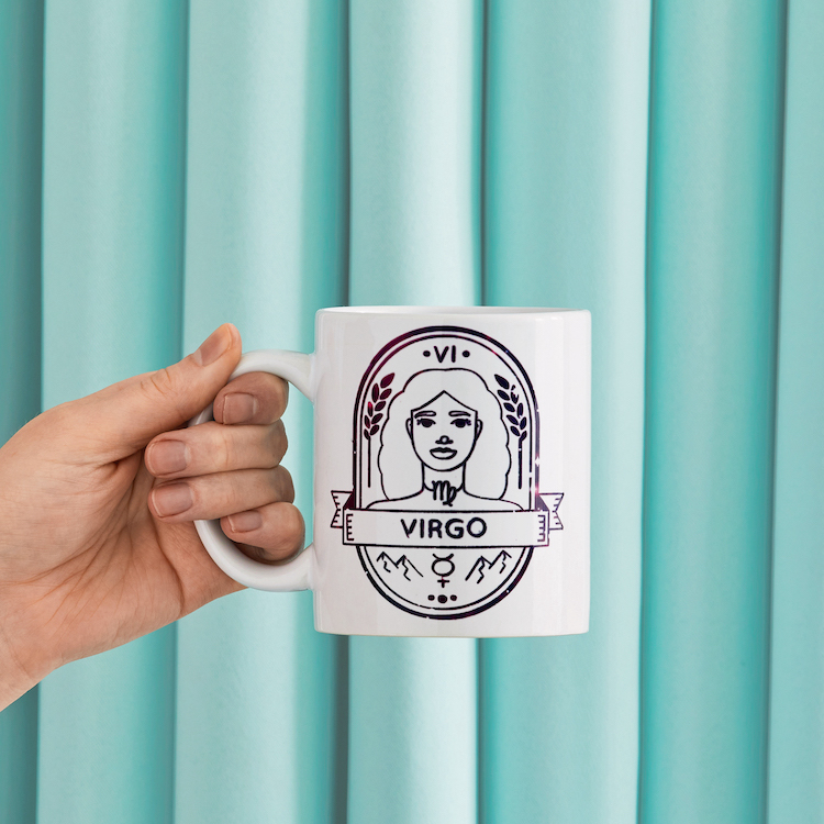 """Hand holding mug with """"Virgo"""" Zodiac symbol in front of blue background"""
