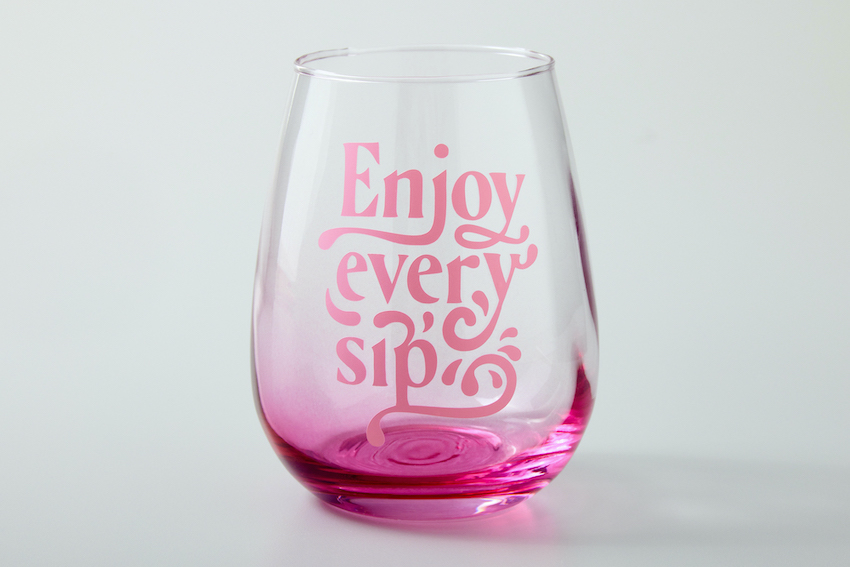 """A photo of a pink wine glass that read, """"enjoy every sip."""""""