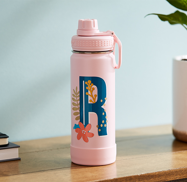 """A pink water bottle with a blue, floral monogram of the letter """"R"""" on it."""