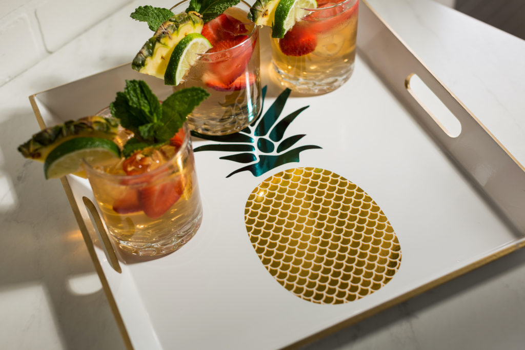 Photo of a drink tray with a golden pineapple on it.