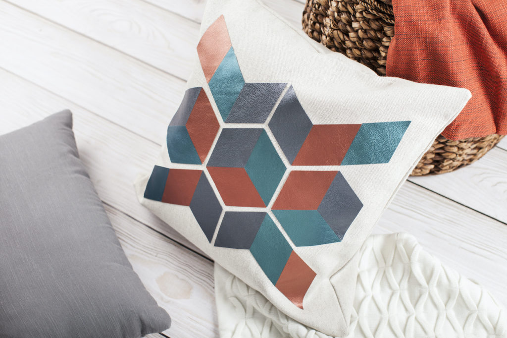 A pillow with a printed geometric pattern, surrounded by other cozy elements like pillows and blankets.