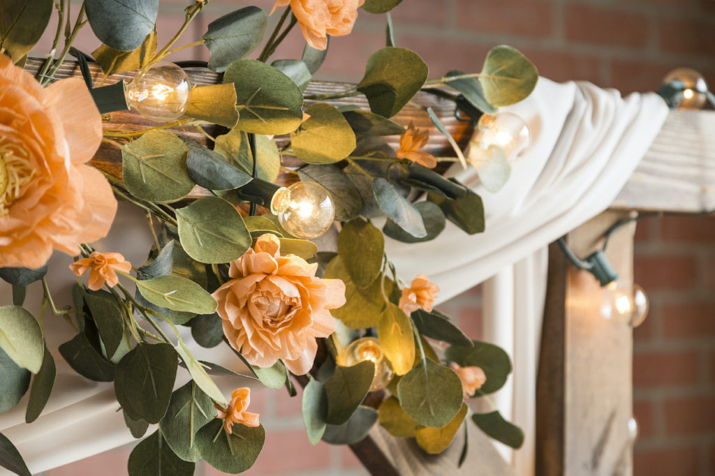 A garland of bright paper flowers wrapped around string lights on a patio frame.