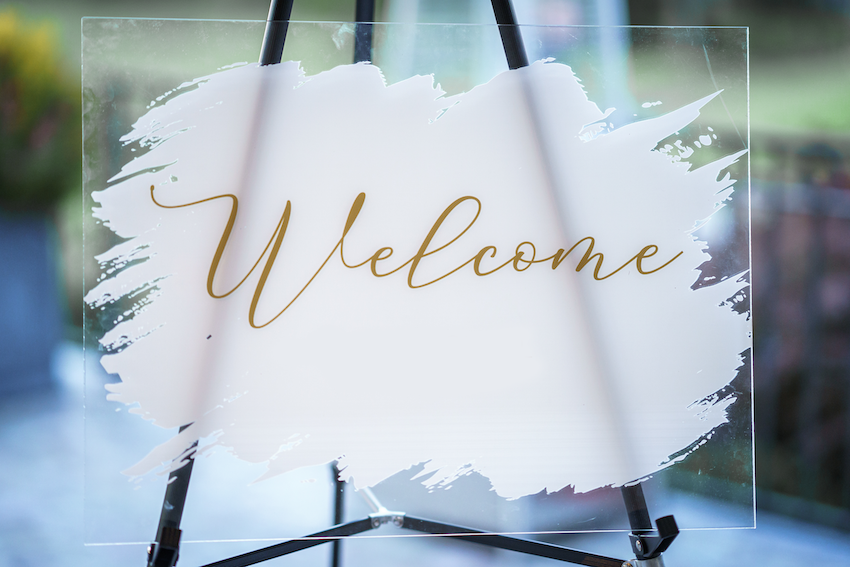 """Acrylic sign with """"Welcome"""" printed on it"""