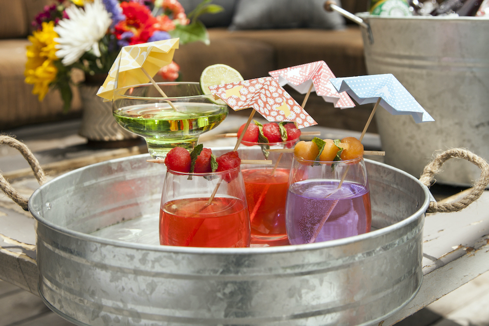 Photo of a metal try holding a variety of colorful drinks, with DIY paper straw umbrellas.