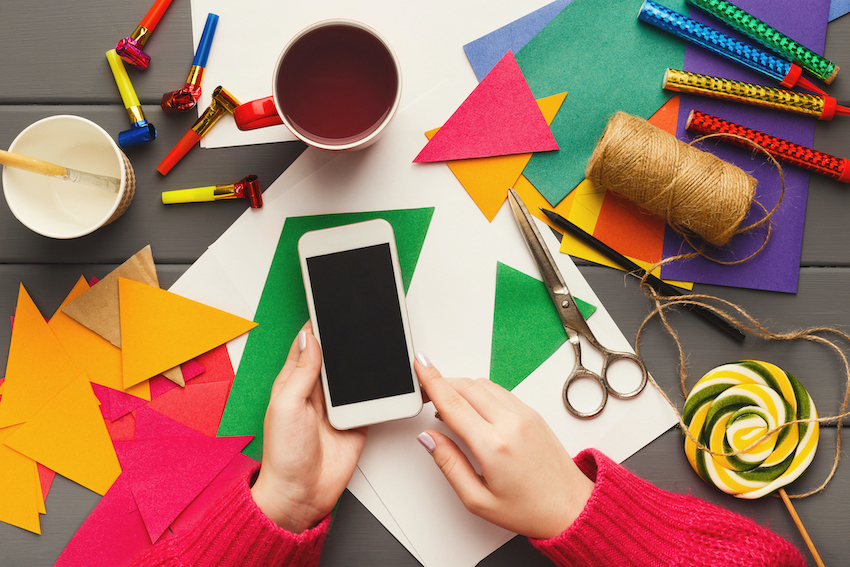 Craft supplies on table and phone in woman's hands