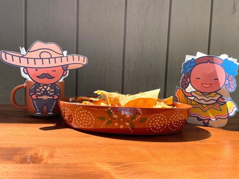 Folklorico girl and Mariachi napkin holder and utensil cup on table with bowl of tortilla chips