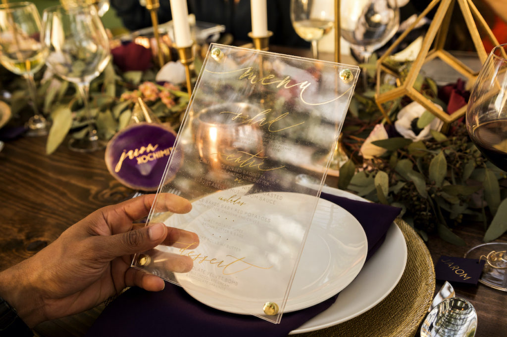 A hand holds a clear, acrylic menu gilded with golden script that lists the dinner menu items.
