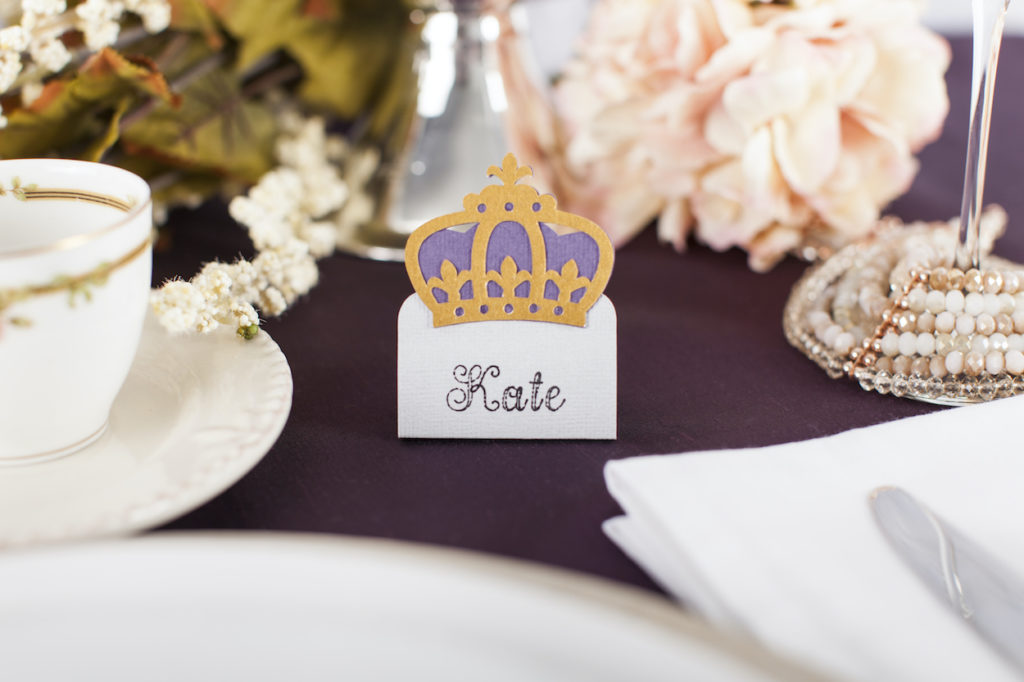 A regal looking name tag sits next to a ceramic place setting.