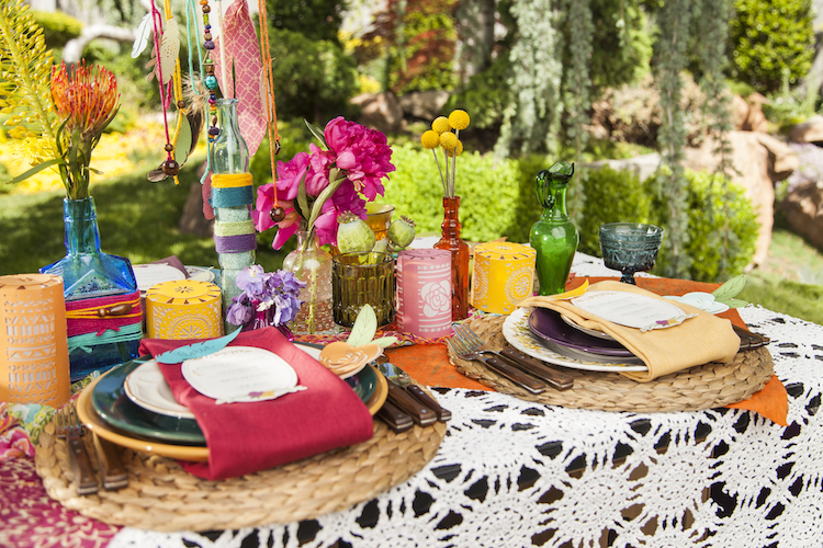 A photo of a bohemian inspired tablescape with colorful flowers and place settings.