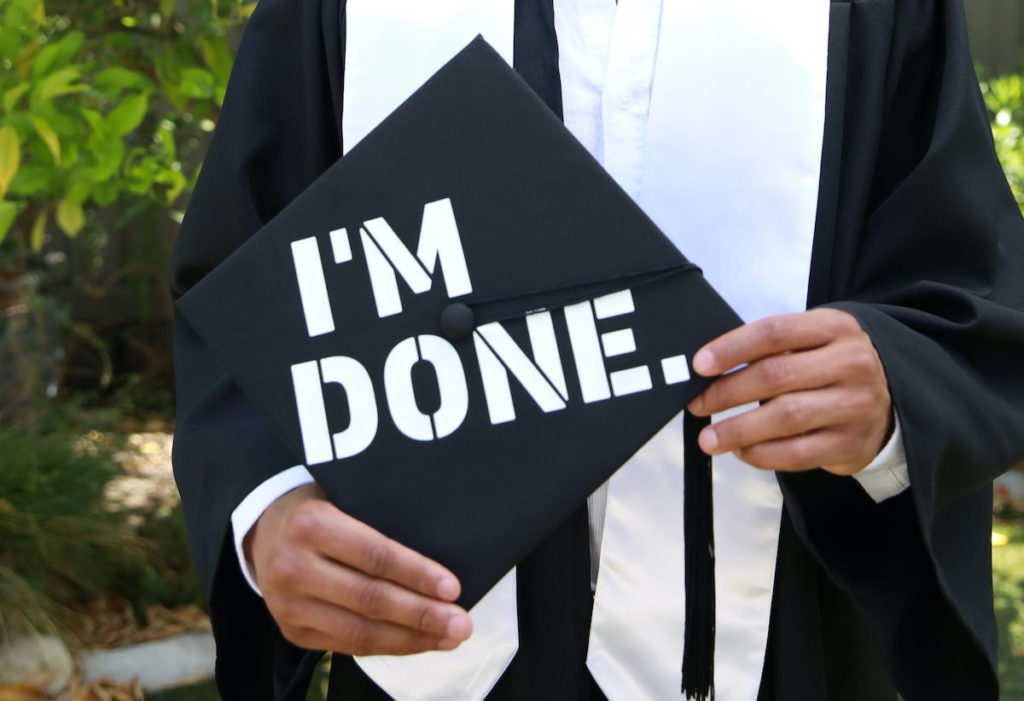 """Graduation cap design reading """"I'm Done"""" being held by a student."""
