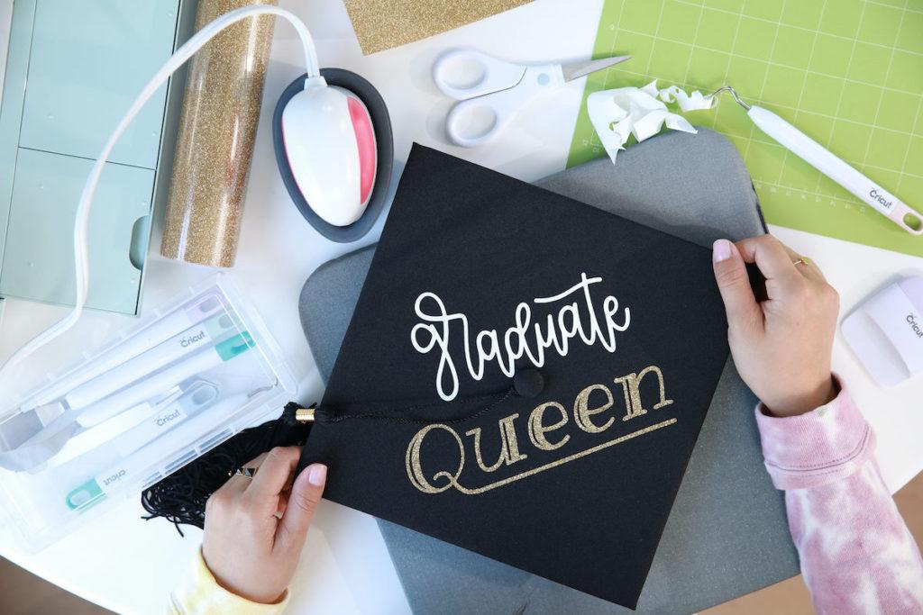 "Hands crafting a black graduation cap design that reads ""graduate queen"" on top with cursive font"