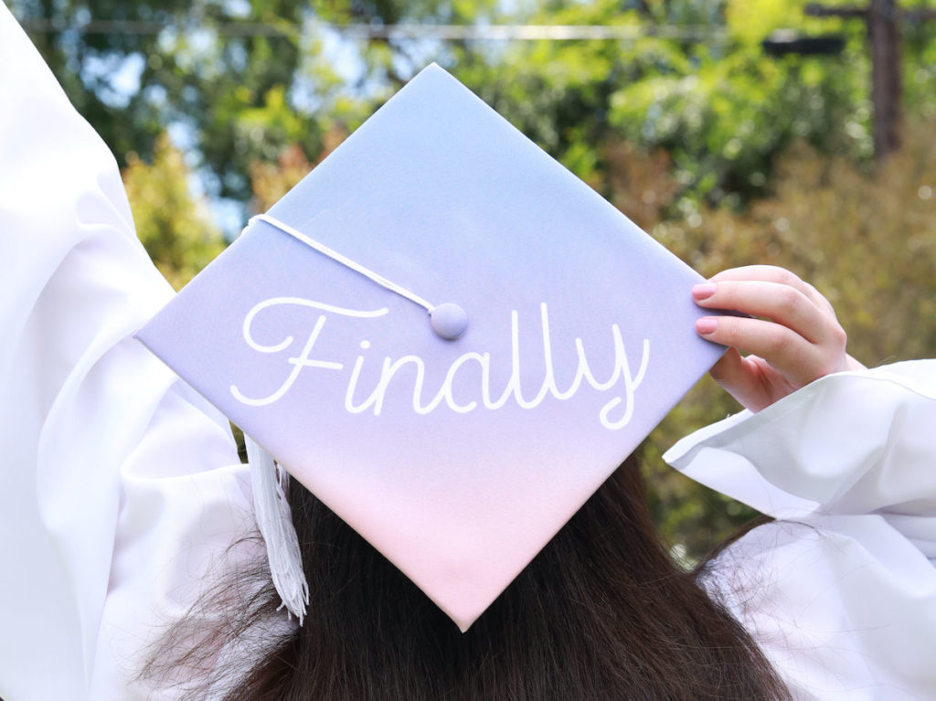 """A gradient purple and pink grad cap sits atop a student's head. The graduation cap design reads """"Finally"""" in white font on top."""