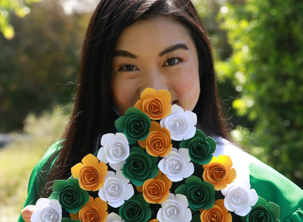 A girl holds up a grad cap in front of her face– the graduation cap design is covered in yellow, green, and white paper flowers.