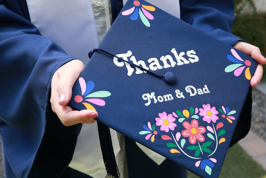 """A girl holds out a grad cap that reads """"Thanks mom and dad"""". The graduation cap design is blue and embellished with colorful vinyl flowers."""