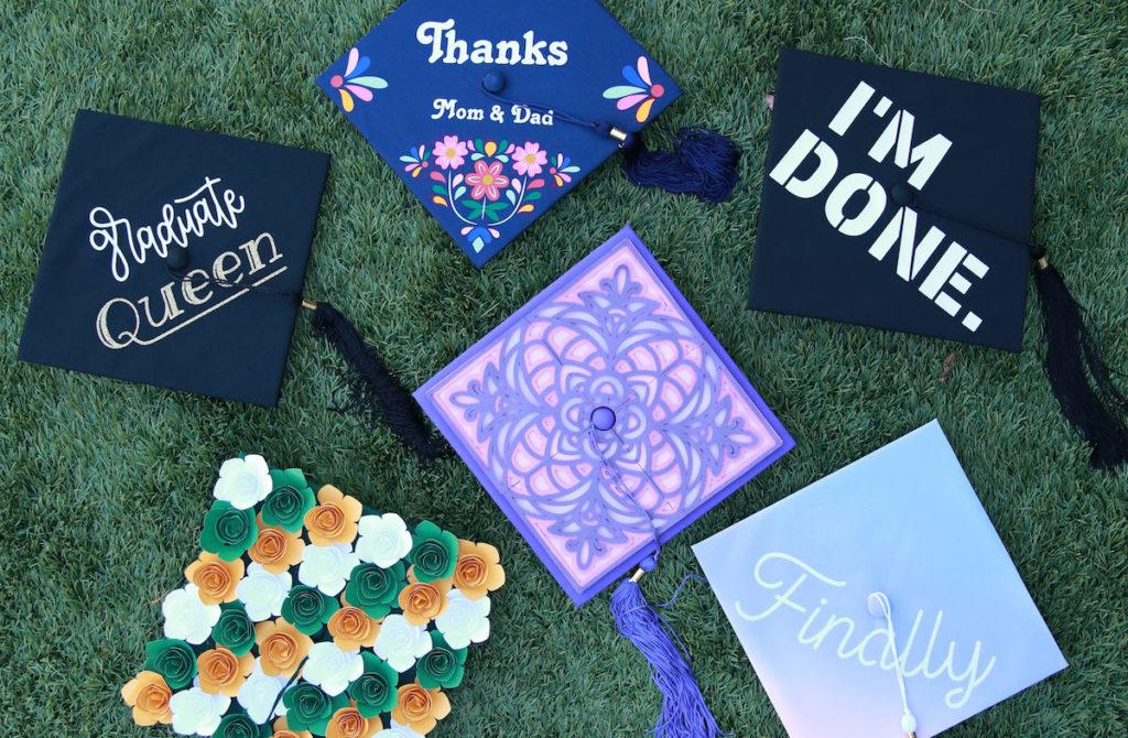 Graduation cap designs sitting on green grass.
