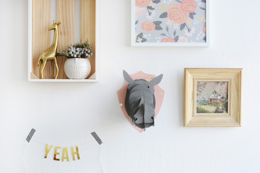 """Interesting art and photo frames sit along a wall, with a banner that reads """"yeah"""" and a paper rhinoceros head."""