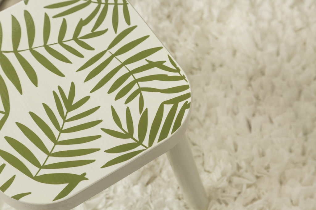 A trendy stool with palm leaf vinyl decals sits on a white fluffy rug.