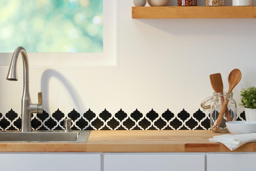 Black vinyl pattern is applied as a backsplash to a beautiful minimalist kitchen.