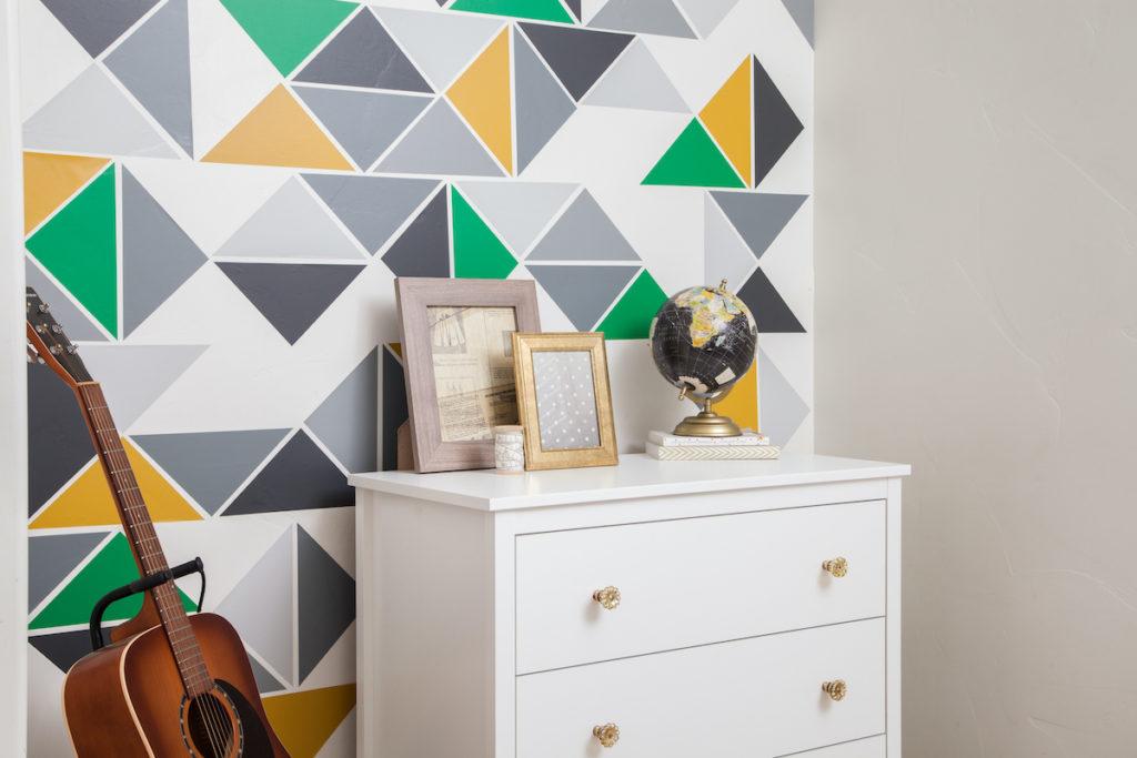 A geometric wall design sits behind a white bookshelf