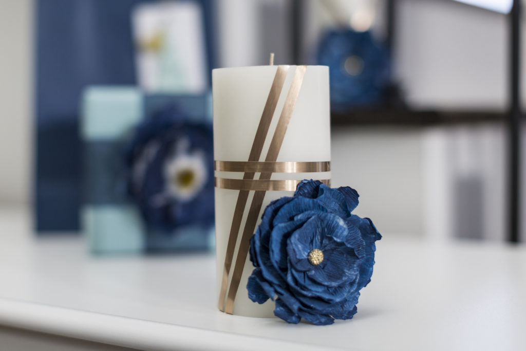 Gold accented candle with blue flower decoration