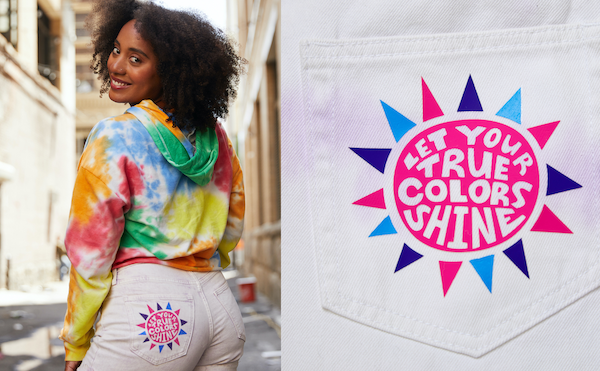 The first Pride outfit idea features a pink, blue, and purple sunburst patch that is ironed onto a white denim shorts pocket.
