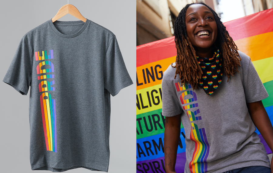 """A rainbow t-shirt decal that reads """"Pride"""" is being worn by a person standing and smiling in front of a Pride flag."""