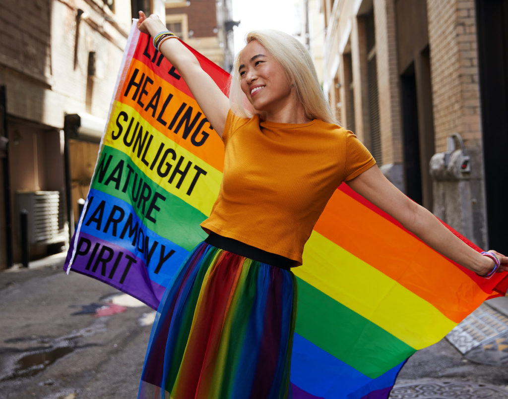 A woman with bright blonde hair and a rainbow skirt holds up a Pride flag in an alleyway