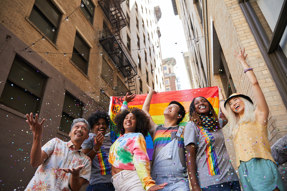 A group of diverse young millennials wearing colorful clothing hold a pride flag as they march through an alleyway