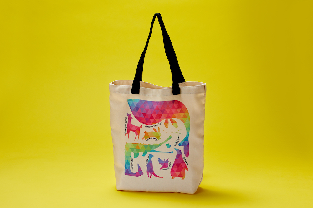 A colorful pattern of animal silhouettes is printed on a tan tote bag