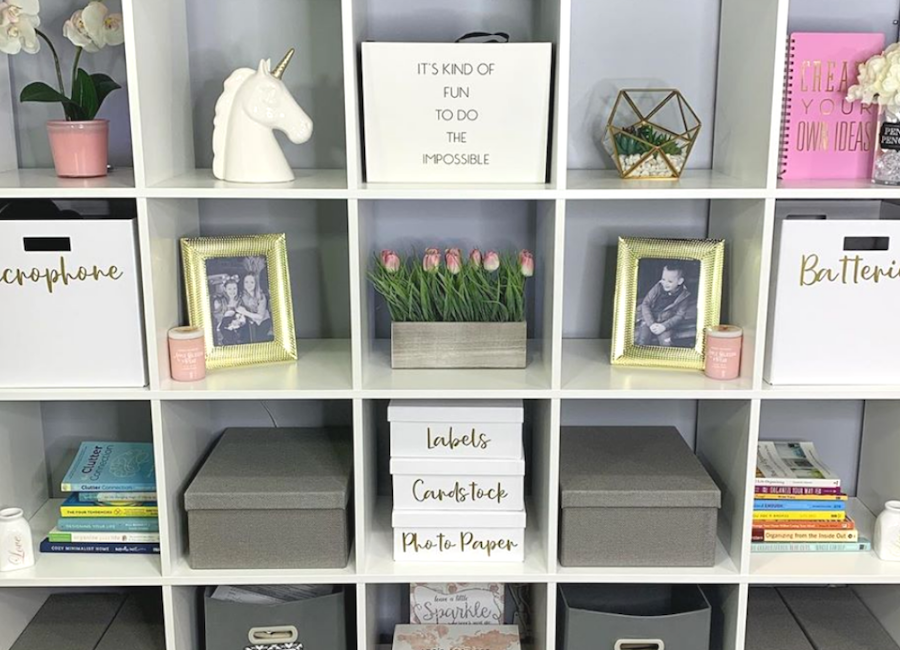 Labeled bins and cubes sit neatly inside a cubed shelving unit surrounded by gold and gray decor and accents.