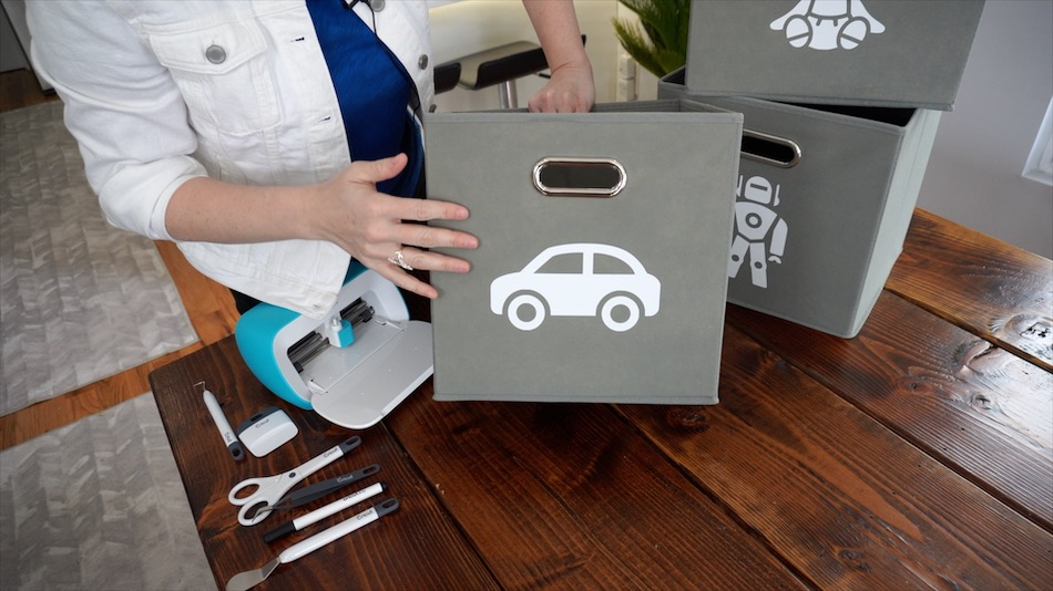 Cassandra demonstrates how to add vinyl decals and logos to felt cube bins.